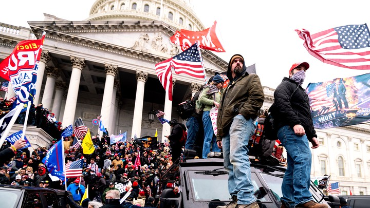 Trump supporters stand and wave flags on the steps of the U.S. Capitol building.