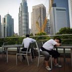 A waitress sleeps as she take a break at a restaurant located in the Pudong financial district of Shanghai in 2013.