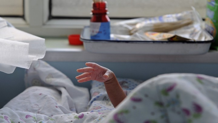A baby stretches its hand from under a quilt in a hospital