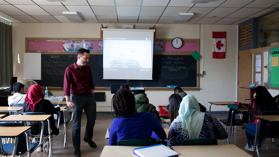 A teacher stands at the front of a classroom in Canada; students sit at desks, a few of whom are wearing hijabs, one of whom has dreadlocks.