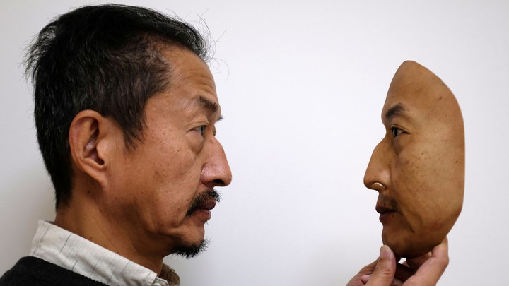 A man holds a realistic replica of a face.