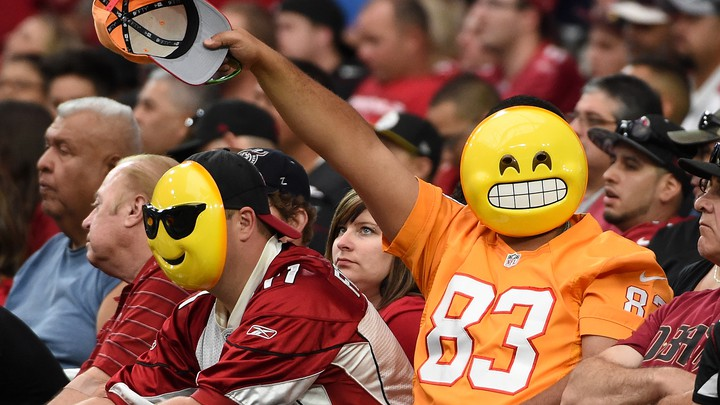 Fans wearing emoji masks wave from the stands at an NFL game.