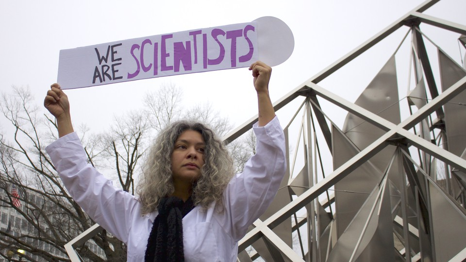 """Dr. Yamilé Molina holds a sign saying 'We Are Scientists' during the Women's March on Washington on Saturday, January 21, 2017. She stands next to the """"Solar Delta"""" outdoor sculpture at the National Air and Space Museum."""