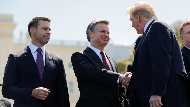 Christopher Wray shakes Donald Trump's hand as Kevin McAleenan looks on.