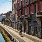 photo: A lone cyclist passes along the banks of the Navigli canal system in Milan. The city is now cautiously exploring how to safely reopen.