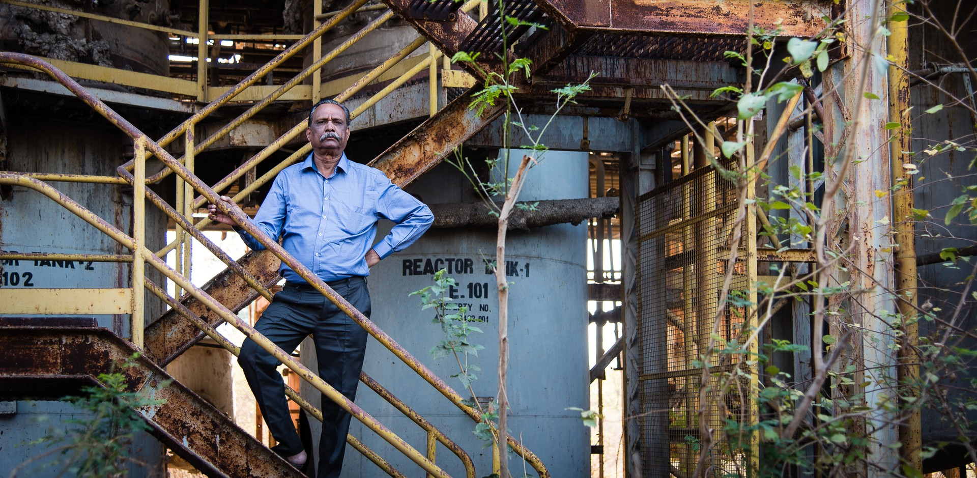 T. R. Chouhan stands on stairs at the ruins of the Union Carbide factory in Bhopal