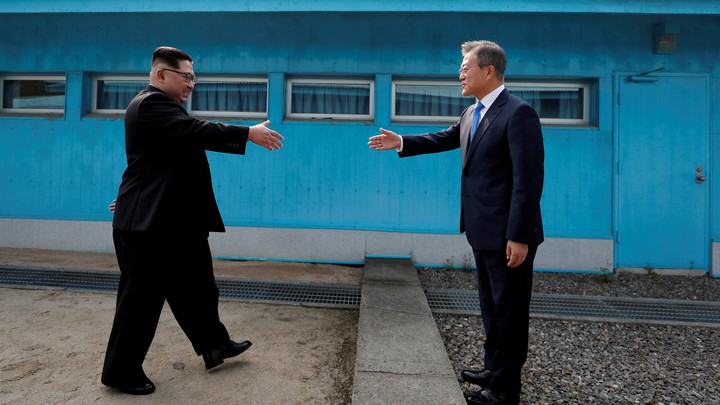 Kim Jong Un and Moon Jae In about to shake hands at the border