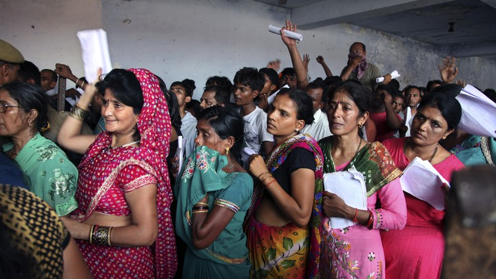 Indian Hindu devotees stand in a queue to register for a pilgrimage to the Hindu holy site of Amarnath on July 2, 2015.