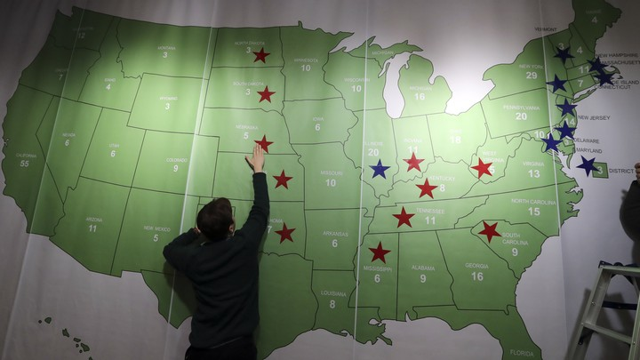 A man reaches up to touch a map of the United States decorated with red and blue stars.
