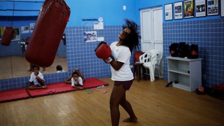 A girl stands next to a punching bag, looking like she is about to punch.