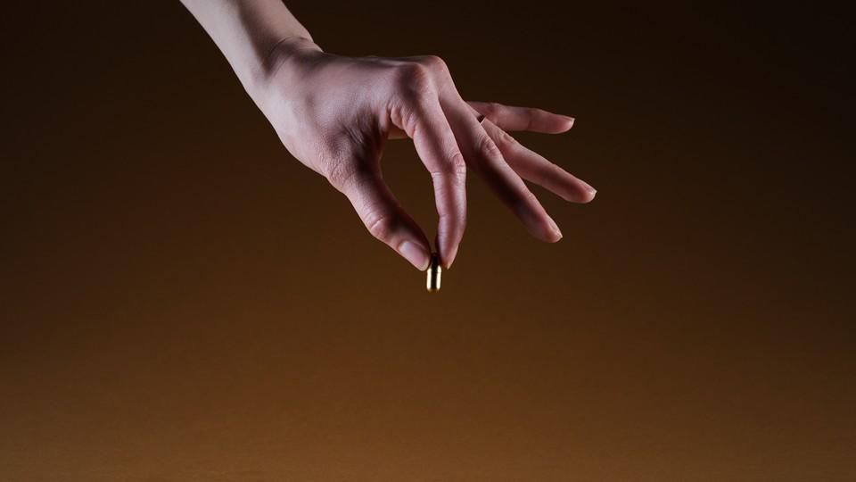 A hand holding a golden pill