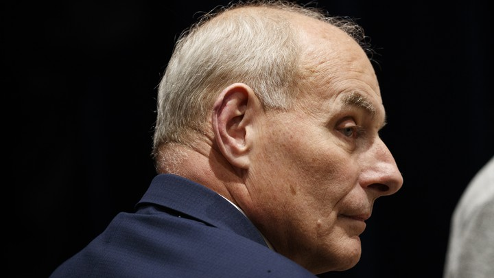 Former White House Chief of Staff John Kelly is seen in profile. The background behind him is black and he's wearing a navy suit.