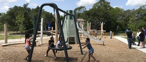 This picture shows a few children playing on the swings at a park.