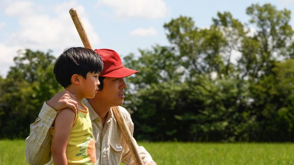Alan Kim and Steven Yeun in a green field in 'Minari'