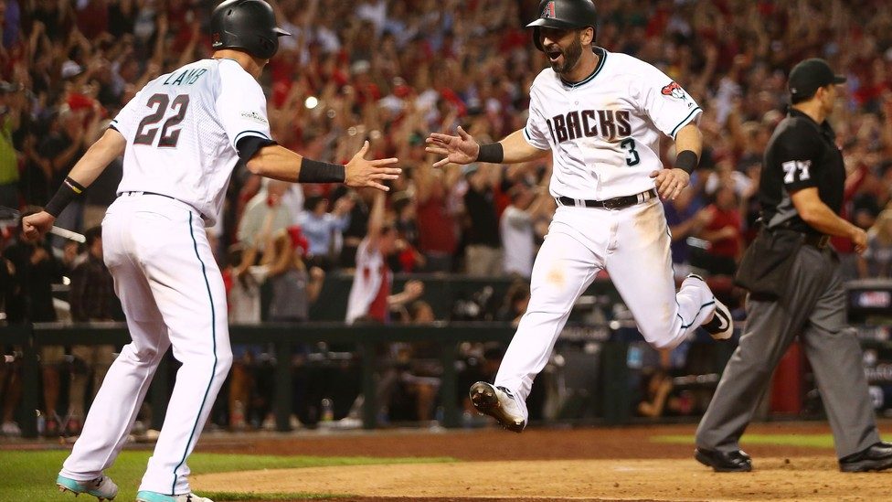 The Arizona Diamondbacks second baseman Daniel Descalso celebrates with the third baseman Jake Lamb after scoring runs in the 2017 National League wildcard playoff baseball game against the Colorado Rockies at Chase Field.