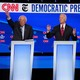 Vermont Senator Bernie Sanders, standing next to former Vice President Joe Biden and Senator Elizabeth Warren of Massachusetts, all behind lecterns on a stage, raises his hand during the fourth Democratic primary debate.