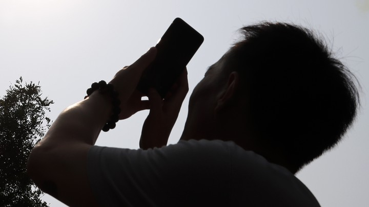 A backlit man points his cellphone toward the sky
