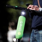 A man stands next to an electric scooter