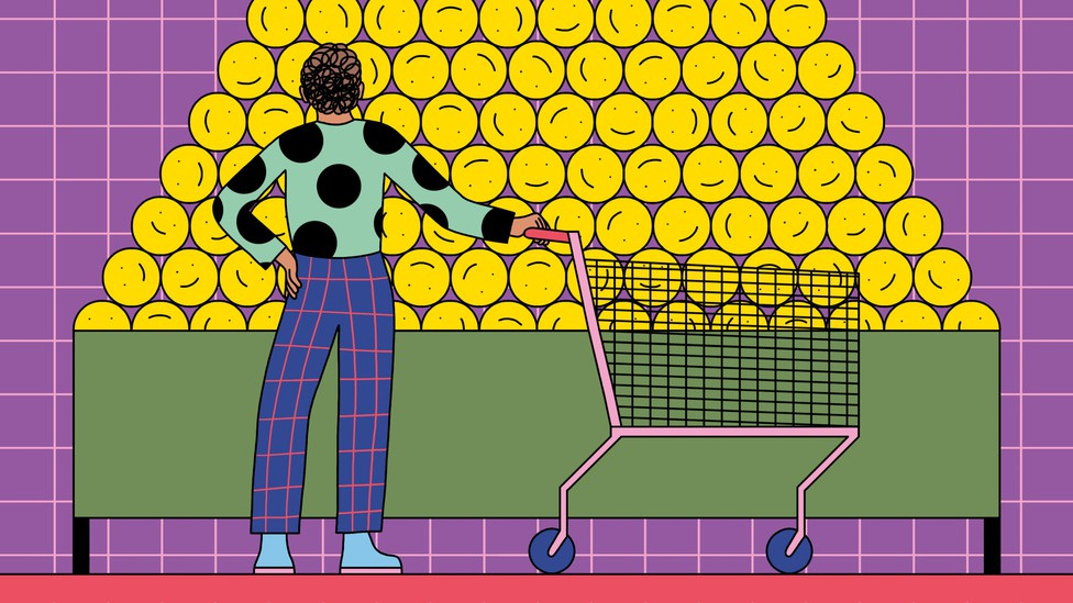 A person with a shopping cart gazes at a large pile of smiley faces
