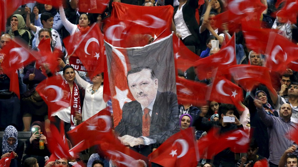 A portrait of Turkey's President Tayyip Erdogan is seen as supporters wave flags before his speech at the Ethias Arena in Hasselt, Belgium, May 10, 2015.