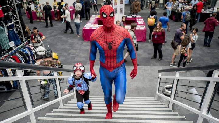 A man dressed as Spider-Man walks up stairs with his daughter.