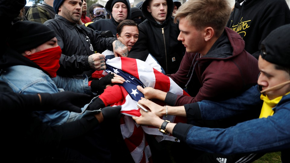 People in sweatshirts and jackets grab at an American flag.