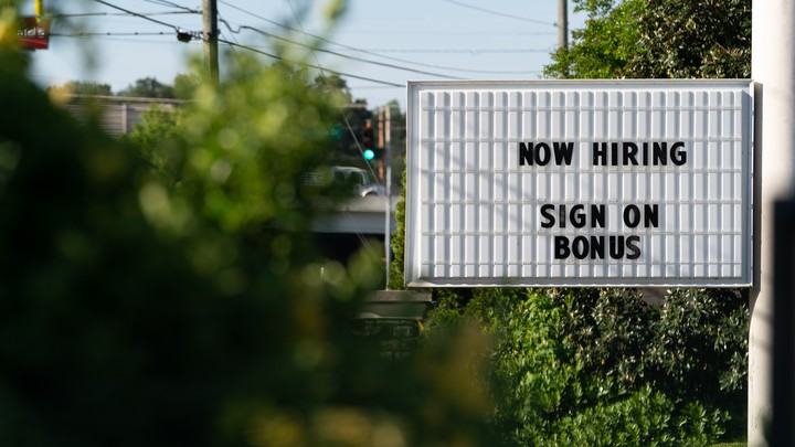 """A sign that says """"Now hiring"""" and """"Sign on bonus."""""""