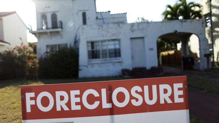A foreclosure sale sign sits in front of a house in Miami Beach.