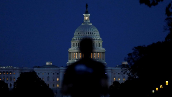 Someone walks past the U.S. Capitol building at dusk.