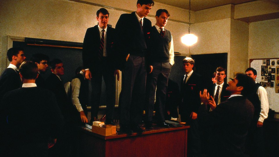 """In a scene from """"Dead Poets Society,"""" students stand on a desk in a classroom."""
