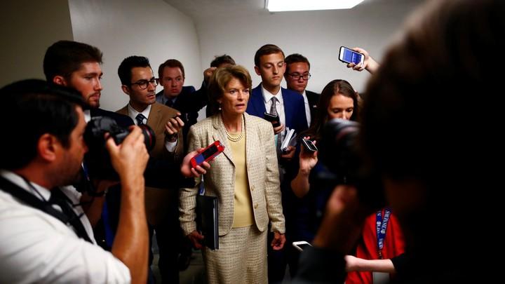 Senator Lisa Murkowski stands with reporters on Capitol Hill.