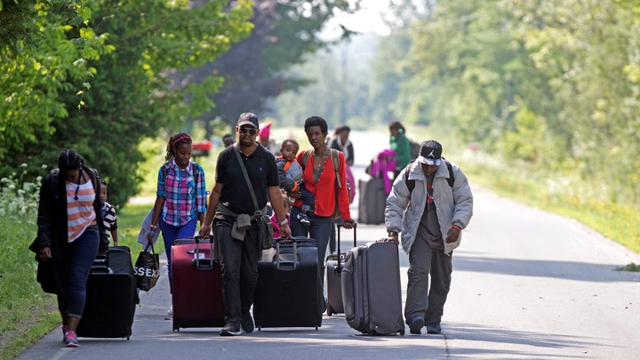 Asylum seekers walk down Roxham Road to cross into Quebec at the U.S.-Canada border in 2017.