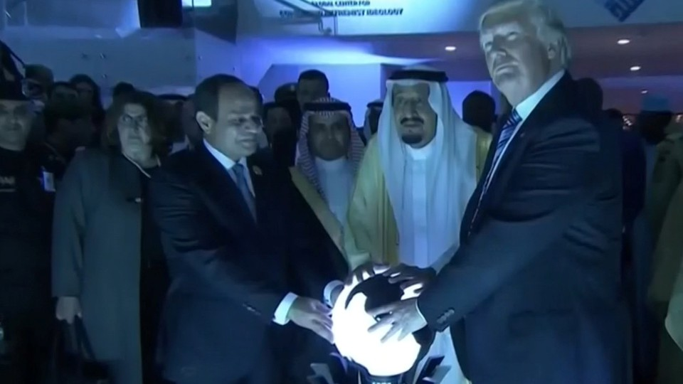 Donald Trump places his hands on a glowing orbin Riyadh, Saudi Arabia, in May2017.
