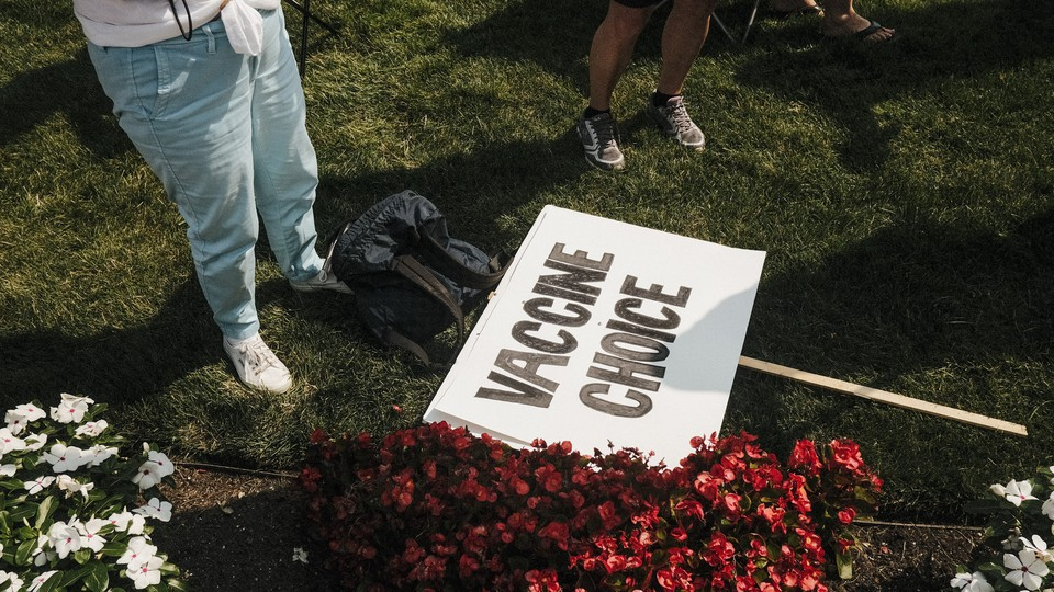 """A photo of the legs of a person standing on a patch of grass next to a placard on the ground that reads """"Vaccine Choice"""""""