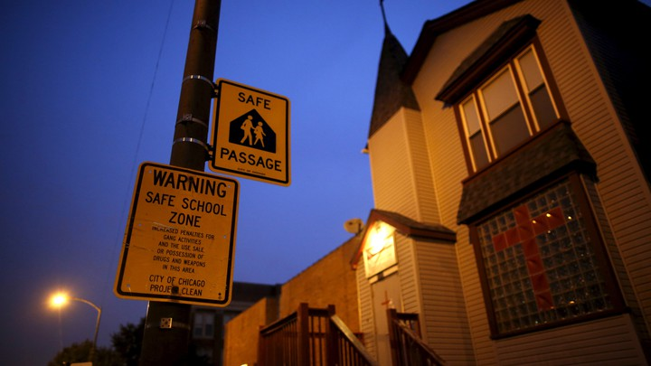 """Taken at night, the photo shows a yellow safe-passage sign reading """"Warning Safe School Zone"""""""