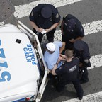 Four New York City police officers arresting a man.