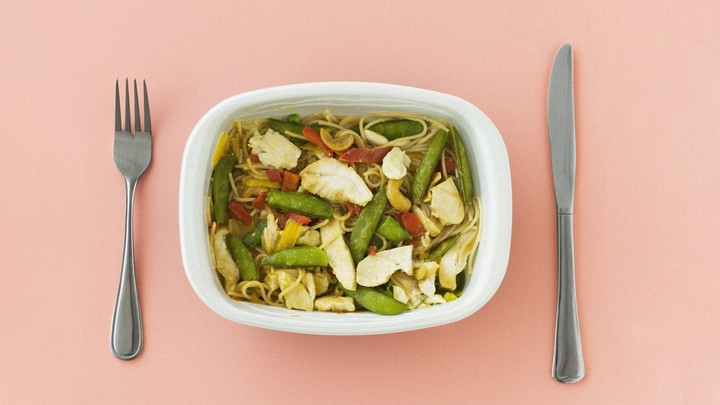 A microwave-dinner plate of pasta with chicken and vegetables