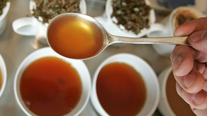 A hand holds a spoon full of tea over cups of brewed tea and tea leaves.