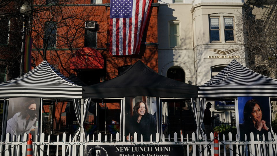 Large photos of Vice President Kamala Harris hang outside a restaurant in Washington, D.C. Hanging off a building in the background is a giant American flag.