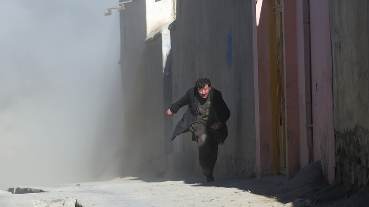 A man runs from dust that followed an attack on a Shiite cultural center in Kabul in 2017.
