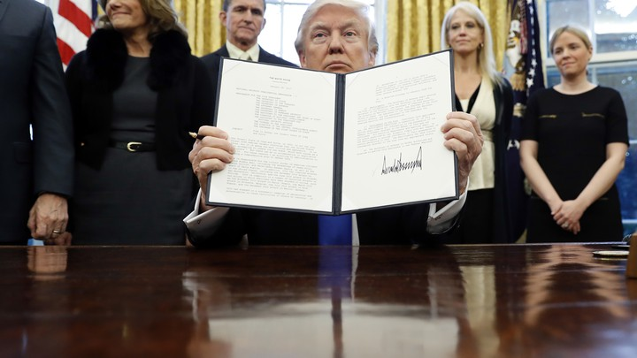 "President Donald Trump holds up a signed presidential memorandum that directs his administration to ""develop a comprehensive plan to defeat ISIS."""