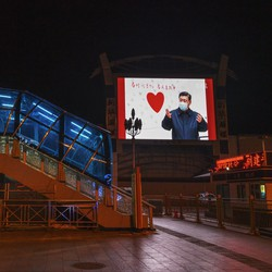 A large monitor shows an image of Chinese president Xi Jinping wearing a mask in an empty station.