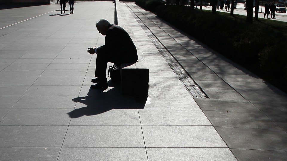 The silhouette of a man looking at his phone as he sits on a long bench