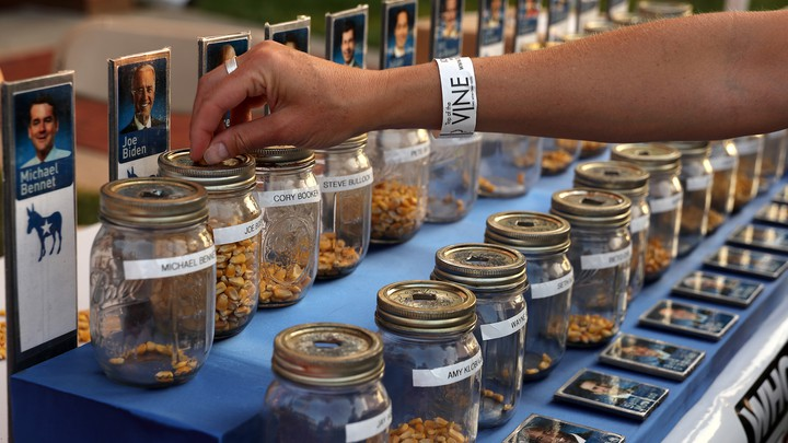 A voter drops a kernel of corn in a jar for the Iowa State Fair corn poll.