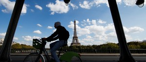 A cyclist passes the Eiffel Tower in Paris.