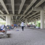 A photo of an encampment of homeless people underneath an elevated highway in downtown Houston.
