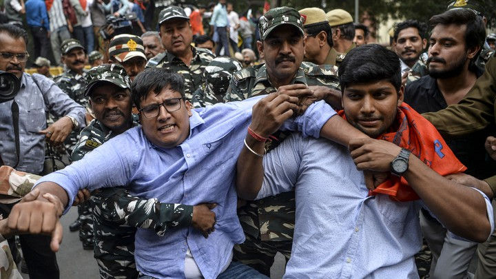 Security personnel grab student protesters during a demonstration.