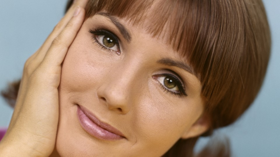 Woman smiling with hand resting on her face