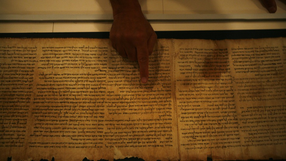 A person points with their index finger at the Isaiah Scroll.