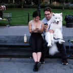 Groups of people look at their phones while sitting in Washington Square Park in Manhattan.